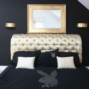 Styl glamourowej sypialni bez wątpienia narzuca łóżko z zagłówkiem tapicerowanym złoconą tkaniną. Efekt dopełniają kinkiety oraz lustro oprawione w ramę o barwie złota. Projekt: Magdalena Konochowicz. Fot. Bartosz Jarosz.
