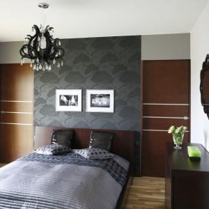 Ściana za łóżkiem, wykończona panelami oraz tapetą, jest najmocniejszym detalem w aranżacji wnętrza. Efekt dopełniają dwa, czarno-białe zdjęcia. Projekt: Anna Gruner. Fot. Bartosz Jarosz.