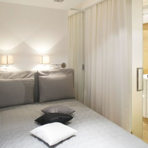 W nawet najmniejszym mieszkaniu warto wygospodarować miejsce na pełnowymiarowe, wygodne łóżko do spania. Jeśli nie mamy oddzielnego pokoju na sypialnię, możemy je odgrodzić elegancką zasłoną i ustawić łóżko w strefie dziennej. Projekt: Monika i Adam Bronikowscy. Fot. Bartosz Jarosz.