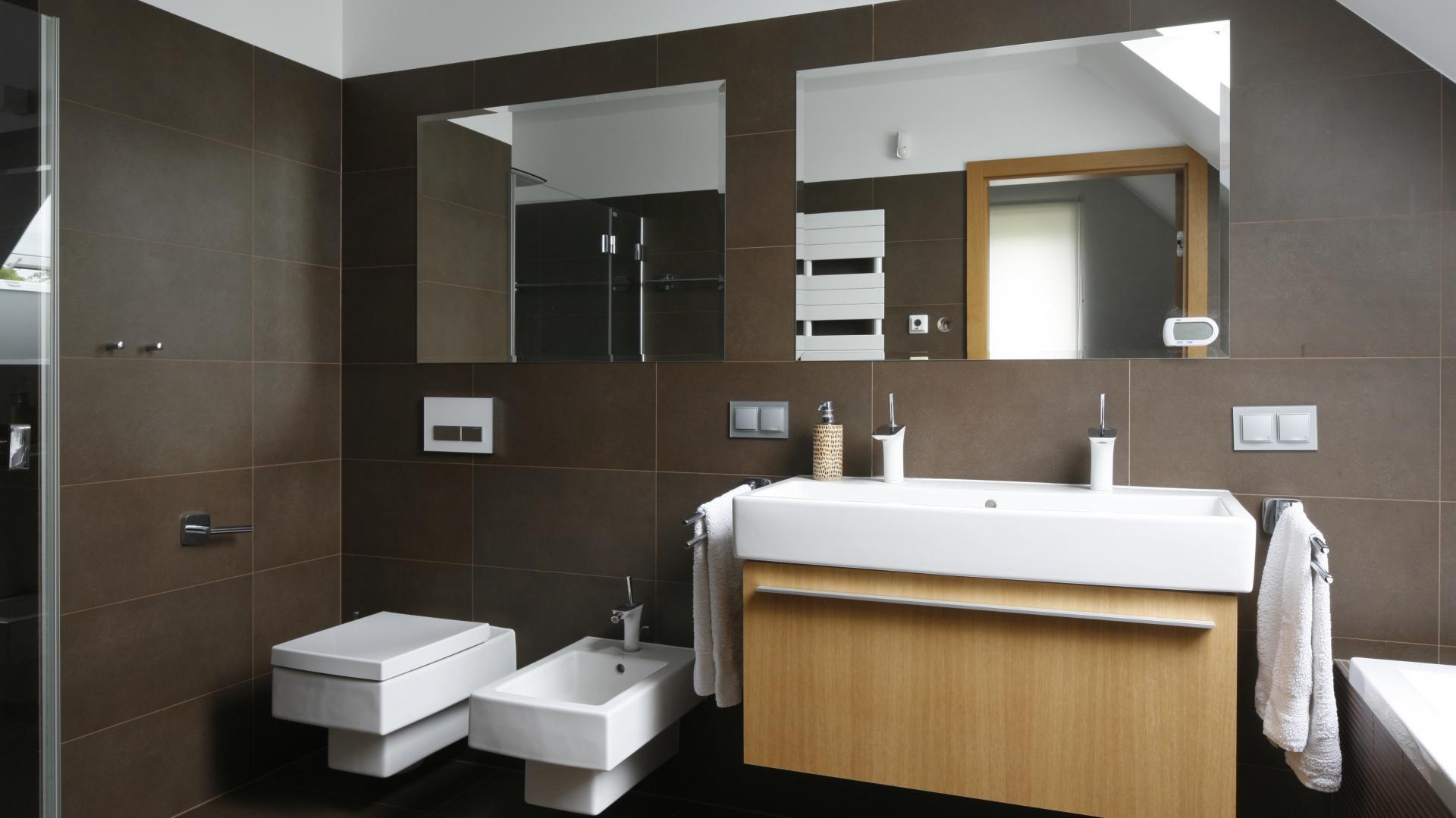 Aranżację łazienki oparto na stonowanym zestawieniu kolorystycznym. Ciemne brązy przełamano bielą ceramiki i ciepłym odcieniem szafki podumywalkowej. Umywalka meblowa z dwoma otworami na baterię to praktyczne rozwiązanie, które świetnie sprawdzi się w łazience dla dwojga. Fot. Bartosz Jarosz.