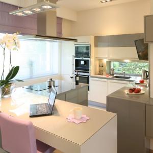 Przestrzeń kuchni skąpana jest w delikatnych szarościach – to główny kolor blatów i zabudowy kuchennej. Fronty szafek utrzymane są natomiast w ciepłej  bieli. Projekt: Monika i Adam Bronikowscy. Fot. Bartosz Jarosz.