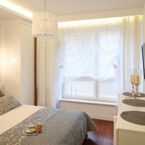 Połyskujące lampy, błyszczące dodatki, blask i przepych to tylko niektóre elementy tej aranżacji. Odrobinę luksusu wprowadza dekoracyjna ściana za łóżkiem wykończona szarą tapetą. Projekt: Małgorzata Mazur. Fot. Bartosz Jarosz.
