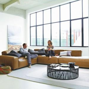Uniwersalny kolor sofy Mio marki Rolf Benz sprawia, że pasuje ona zarówno do nowoczesnego salonu, jak i bardziej tradycyjnego wnętrza. Zawiera praktyczny moduł pełniący rolę stolika kawowego. Model dostępny w Studio Asymetria. Fot. Studio Asymetria.