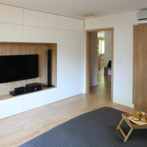 Ściana telewizyjna może służyć również praktycznemu przechowywaniu. Nowoczesna zabudowa została zaprojektowana w taki sposób, w jej centrum mógł zmieścić się duży telewizor oraz głośniki.  Projekt: Małgorzata Błaszczak. Fot. Bartosz Jarosz.