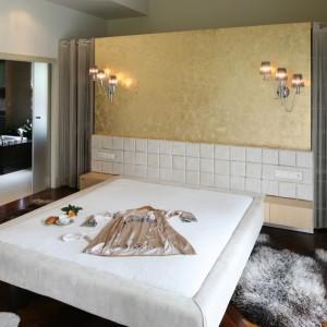Potrójne, eleganckie kinkiety, na ścianie za łóżkiem subtelnie oświetlają przestronne wnętrze. Lampy eksponują też dekoracyjną fakturę ściany za łóżkiem, podkreślając luksusowy charakter wnętrza. Projekt: Dominik Respondek. Fot. Bartosz Jarosz.
