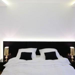Nowoczesna aranżacja sypialni jest bardzo oszczędna, zarówno w kolorze jak i dodatkach. Jedyną dekoracją są lampki nocne w złotym kolorze. Projekt: Agnieszka Hajdas-Obajtek. Fot. Bartosz Jarosz.