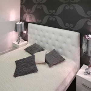 Chociaż sypialnie jest nie wielka, nie brakuje w niej dekoracji. Elegancka tapeta za łóżkiem oraz dekoracyjne lampy marki Kartell sprawiają, że małe wnętrze zyskuje stylowy wygląd. Projekt: Katarzyna Mikulska-Sękalska. Fot. Bartosz Jarosz.