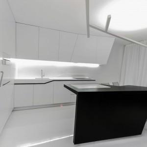 Czerń i biel zdominowały przestrzeń kuchni. Uniwersalne połączenie barw urozmaicają oryginalne kształty wykonanej na zamówienie zabudowy. Projekt: Radomír Minjarík. Fot. Juraj Hatina.