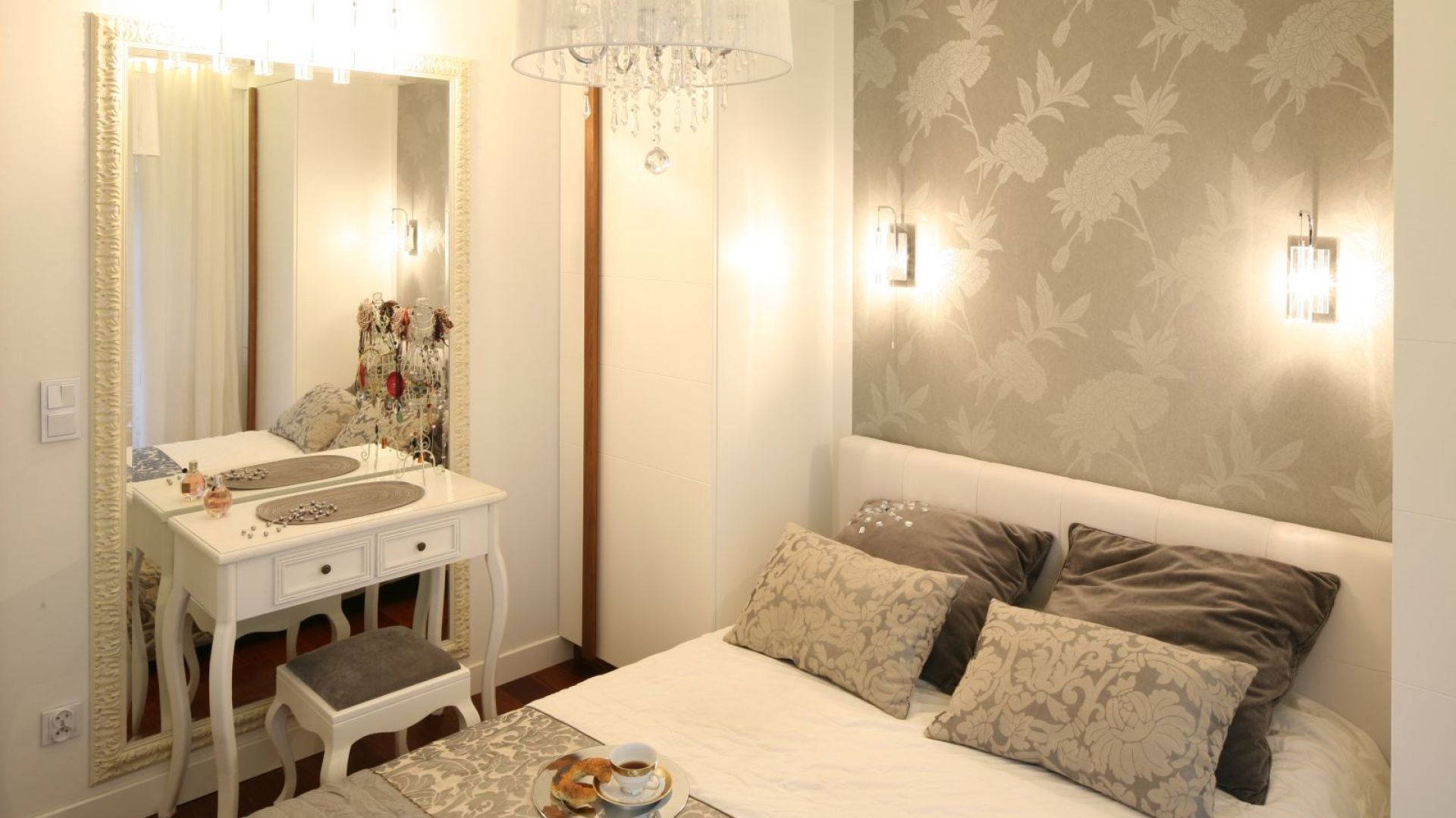 Okrągła lampa z kryształkami podkreśla glamourowy styl jasnej sypialni. Uroku dodają też kinkiety oraz kryształowe oświetlenie toaletki. Projekt: Małgorzata Mazur. Fot. Bartosz Jarosz.