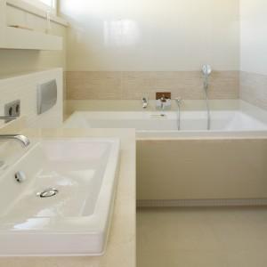 Prostokątna wanna zajmuje niewiele miejsca w łazience, dzięki czemu zmieściły się w niej również wszystkie niezbędne elementy. Projekt: Małgorzata Borzyszkowska. Fot. Bartosz Jarosz.