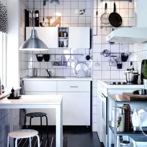 Styl skandynawski jest również idealny do bardzo małych przestrzeni, takich jak ta kuchnia. Białe meble i ściany optycznie powiększają niewielkie wnętrze. Oprócz białych mebli skandynawski styl we wnętrzu budują również industrialne dodatki, jak metalowe lampy i stołki. Fot. IKEA.