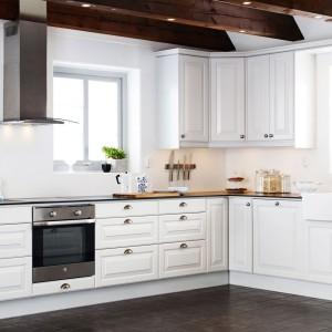 Delikatnie frezowane fronty zabudowy kuchennej nadają urok tej białej kuchni. Śnieżną biel zamykają w ciemnobrązową ramę: od dołu podłoga, a od góry odsłonięte belki stropowe. Fot. Ballingslov.