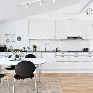 Kuchnia w mieszkaniu wystawionym na sprzedaż przez szwedzką agencję Alvhem Makleri. Typowo skandynawska aranżacja z białymi meblami i kaflami nad blatem oraz podłogą w ciepłym kolorze drewna. Fot. Alvhem Makleri/Fredrik J Karlsson.