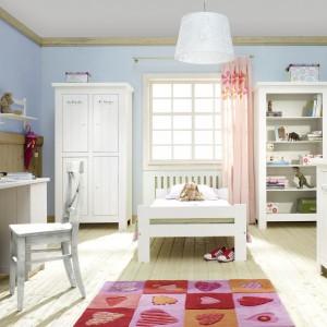 Jeśli decydujemy się na białe meble, warto zadbać o kolorowe tło. Ściany możemy pomalować farbą w kolorze pastelowego różu lub błękitu. Aranżację ociepli drewniana podłoga lub boazeria. Zestaw mebli dziecięcych Barcelona marki Pinio. Fot. Pinio.