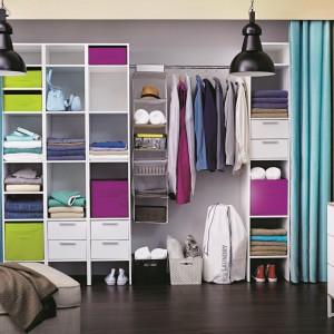 Prostym sposobem na praktyczną garderobę jest ustawienie we wnęce otwartego regału z wieloma półkami. Rolę drzwi przesuwnych mogą pełnić kolorowe zasłony. Fot. Castorama.