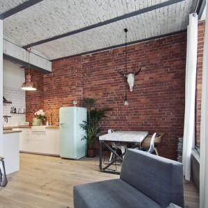 W kuchni sufit podtrzymują odsłonięte, betonowe belki stropowe, potęgujące wrażenie industrialnego wnętrza. Z pofabrycznymi przestrzeniami kojarzą się również duże, wysokie okna, które zostały delikatnie ocieplone jasnymi, przewiewnymi firanami. Fot. RED Real Estate Development.
