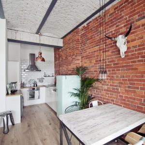 Kuchnię wpasowano w jasną wnękę, w której zabudowa kuchenna w białym kolorze harmonizuje z tradycyjnymi kaflami nad blatem. Aranżacja przestrzeni nawiązuje do stylu skandynawskiego. Fot. RED Real Estate Development.