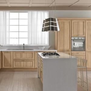 W kolorach drewna pięknie prezentują się kuchnie klasyczne, z frezowanymi, zdobnymi frontami. Tutaj w połączeniu z delikatną szarością tworzą elegancki zestaw. Fot. Cucine Lube, model Silvia.