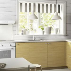 Dolną zabudowę zdobi poziomy rysunek drewna w jasnym kolorze. Razem z bielą na ścianach i białym sprzętem AGD tworzy ona kuchnię w skandynawskim stylu. Fot. IKEA.
