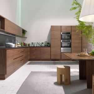 Drewniane meble kuchenne zachwycają głębokim, ciemnym wybarwieniem. Zabudowie kuchennej wtóruje stół jadalniany z litego drewna i towarzyszące mu stołki/pieńki. Fot. La Cucina.