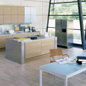 Kolor jasnego dębowego drewna zdobi fronty nowoczesnych mebli. W połączeniu z efektownym, stalowym obramowaniem po bokach oraz delikatnym błękitnym akcentem prezentuje się bardzo elegancko. Fot. Poggenpohl.