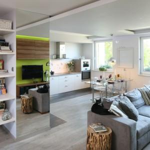 W otwartej strefie dziennej białą zabudowę kuchenną ulokowano na jednej ścianie tworząc elegancki aneks kuchenny. Projekt: Arkadiusz Grzędzicki. Fot. Bartosz Jarosz.
