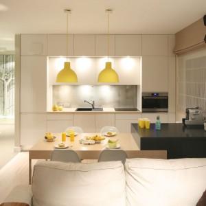Strefa dzienna została zaaranżowana jako wnętrze o charakterze czysto wypoczynkowym. Jemu też zostały podporządkowany wszystkie funkcje pomieszczenia. Stąd zabudowa kuchenna umiejscowiona została tylko na jednej ścianie. Projekt: Lucyna Kołodziejska. Fot. Bartosz Jarosz.