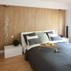 Ściany w sypialni wykończono panelami w kolorze naturalnego, jasnego drewna, korespondującym z parkietem i ramami okiennymi. Modna narzuta oraz poduszki w szarym kolorze stanowią efektowne dopełnienie aranżacji. Projekt: Małgorzata Błaszczak. Fot. Bartosz Jarosz.