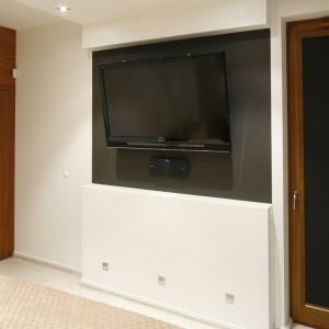 W wieczornym relaksie pomaga telewizor, zainstalowany na ścianie przy pomocy uchwytów. Projekt: Michał Mikołajczak. Fot. Bartosz Jarosz.