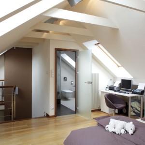 Podłoga, ramy okienne czy futryna wykonane z drewna sprawiają, ze duża przestronna sypialnia na poddaszu wydaje się bardziej przytulna. Projekt: Piotr Gierałtowski. Fot. Tomasz Markowski.