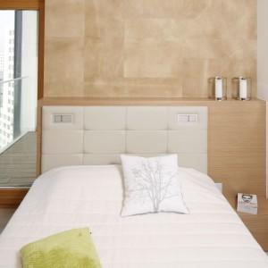 W jasnej, beżowej sypialni ścianę za łóżkiem wykończono drewnianym fornirem oraz naturalną skórą. Dzięki temu sypialnia zyskała bardziej przytulny wygląd nie tracąc swojego nowoczesnego, lekkiego stylu. Projekt: Maciej Brzostek. Fot. Bartosz Jarosz.
