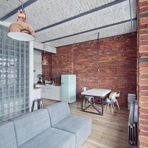 Przestrzeń dzienna łączy w sobie kuchnię, jadalnię oraz salon z dużą, mobilną sofą. Czerwona cegła na ścianie ożywia wnętrze. Fot. RED Real Estate Development.