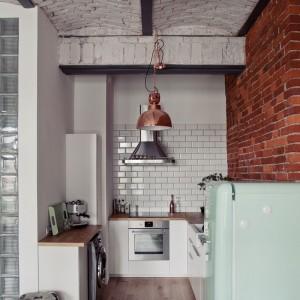 Tradycyjne białe kafle nadają kuchni skandynawsko-prowansalski urok i stanowią ciekawą kombinację z czerwoną i szarą cegłą na ścianie i suficie. Fot. RED Real Estate Development.