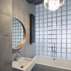 Sufit w łazience podtrzymuje betonowa beka stropowa, potęgując surowy klimat, panujący we wnętrzu. Fot. RED Real Estate Development.