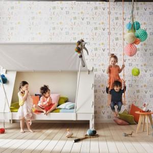 Łóżko przypominające kształtem namiot wprowadzi do wnętrza atmosferę rodem z biwaku. Dla równowagi ścianę można ozdobić tapetą w literki z serii Summer Camp marki JVD. Fot. JVD.