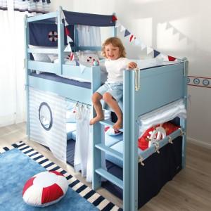 Warzenia o dalekich podróżach statkiem mogą być inspiracją do stworzenia marynarskiego pokoju dziecka, utrzymanego w biało-granatowej kolorystyce. Centralnym punktem aranżacji jest łóżko przypominające formą okręt. Fot. The Baby Cot Shop.