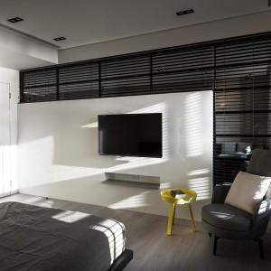 Sypialnię od strefy dziennej oddziela częściowo przeszklona ścianka. Jeśli domownicy potrzebują prywatności, mogą zasłonić zawieszone w przeszkleniach czarne żaluzje. Projekt: Circle Huang i Gina Chou. Fot. Hey! Cheese.