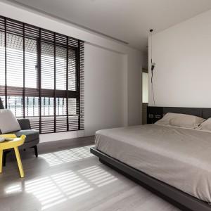 W sypialni, zdominowanej przesz szarości i kolory ziemi, żywym akcentem jest niewielki, żółty stolik. Projekt: Circle Huang i Gina Chou. Fot. Hey! Cheese.
