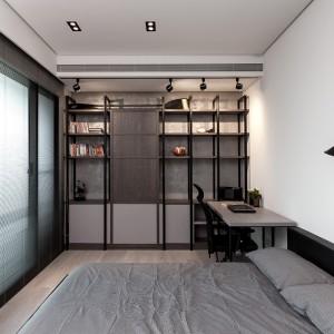 Ściankę przy biurku zabudowano regałem z lekkimi, otwartymi półkami, które podświetla industrialne oświetlenie zamontowane w suficie. Projekt: Circle Huang i Gina Chou. Fot. Hey! Cheese.