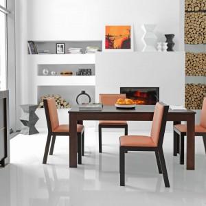 W inspirowanych włoskim designem meblach Modern uwagę zwracają charakterystyczne intarsje w kontrastowym kolorze na frontach mebli. Piękne, naturalnie wyglądające słoje zostały skontrastowane z nowoczesną geometrią intarsji. Prosta linia stołu odnosi się do czystej formy kolekcji, dając domownikom wolność w aranżacji wnętrza. Fot. Vox Meble.
