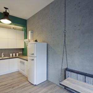 Minimalistyczna kuchnia w stylu loft. Śnieżną biel białych frontów zabudowy kuchennej skomponowano z betonową  ścianą i industrialnym oświetleniem. Ciekawym dodatkiem jest siedzisko-huśtawka na łańcuchach. Fot. RED Real Estate Development.