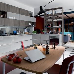 Szare, lakierowane fronty w wysokim połysku, połączone z industrialnymi lampami i metalowym parawanem, oddzielającym kuchnię od salonu wprowadzają do wnętrza industrialną atmosferę. Fot. Veneta Cucine.