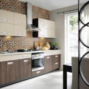 Dwukolorowa kuchnia Tafne z linii Family Line, będącej zbiorem modułów, które można dowolnie ze sobą zestawić. Zabudowa tworzy niezwykle funkcjonalną i dobrze zaplanowaną przestrzeń kuchni o niespełna sześciometrowym metrażu. Zestawienie barw shiraz wenge/beż połysk buduje w kuchni przytulny nastrój. Fot. Black Red White.