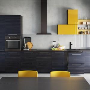 Obudowa szafek wykończona folią melaminowaną imitującą czarne drewno. Asymetryczna górna szafka wykończona folią z połyskiem w kolorze żółtym, który pięknie ożywia ciemną aranżację. Fot. IKEA, kuchnia metod.