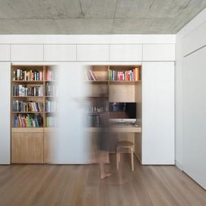 Za drzwiami obok biblioteczki schowano kącik z biurkiem, komputerem i dodatkowymi półkami. W razie potrzeby, w kilka chwil, właściciele mogą stworzyć domowe biuro. Projekt: Normundas Vilkas. Fot. Leonas Garbacauskas.