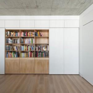 """Ściany w salonie pokrywa wysoka zabudowa, częściowo biała, częściowo w kolorze drewna. Jej """"drewniany"""" segment został zagospodarowany na pojemną biblioteczkę. Projekt: Normundas Vilkas. Fot. Leonas Garbacauskas."""