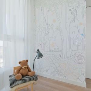 Ścianę wolną od zabudowy pokrywa grafika z sympatycznym motywem zwierząt w lesie. Wzór przypomina dziecięcą kolorowankę. Projekt: Normundas Vilkas. Fot. Leonas Garbacauskas.
