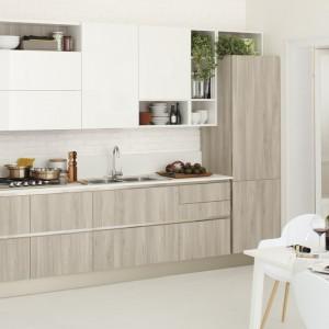 Zabudowa meblowa na jedną ścianę w skandynawskim stylu. Dolne szafki z drewnianym dekorem w kolorze bielonego drewna zestawiono z górnymi w odcieniu ecru i z asymetrycznymi otwartymi półkami. Całość prezentuje się jednocześnie nowocześnie, ale i uniwersalnie. Fot. Veneta Cucine, model Start-Time.Go 28.