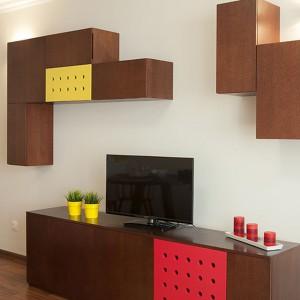 Z perforacjami na frontach zabudowy kuchennej harmonizują ażurowe, kolorowe wstawki w meblach w salonie. Czerwień i żółć urozmaicają drewno w ciemnym wybarwieniu. Projekt: Antonia Saranedelcheva. Fot. Yana Blazeva.