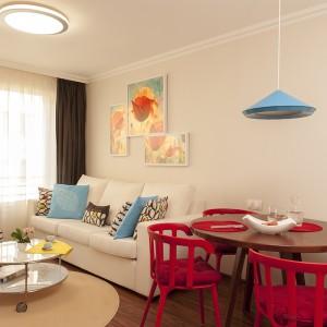 Wisząca nad stołem jadalnianym błękitna, nowoczesna lampa harmonizuje kolorem z poduszkami dekoracyjnymi w strefie dziennej. Projekt: Antonia Saranedelcheva. Fot. Yana Blazeva.